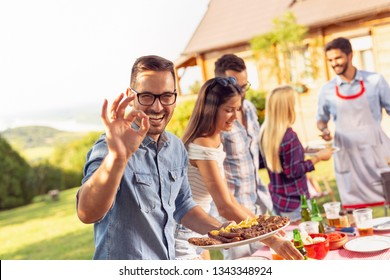 Group of friends making barbecue in the backyard, drinking beer and having fun on a sunny summer day