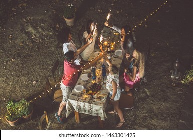 Group of friends making barbecue in the backyard at dinner time. Spending quality time , and eating healthy food outdoor. Lifestyle concept in the evening