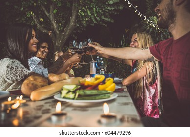 Group of friends making barbecue in the backyard at dinner time