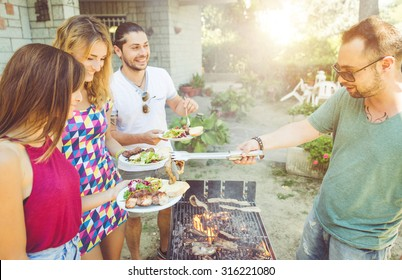 group of friends making barbecue in the garden backyard. friends sharing food and happy moments