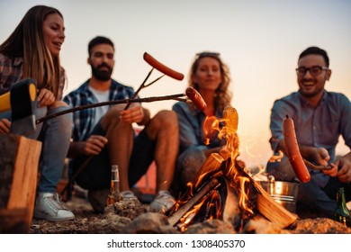 Group of friends making barbecue on the beach.