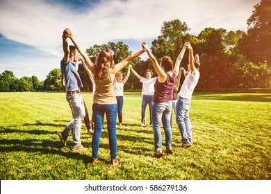Group of Friends Making a Circle and Holding Hands Together