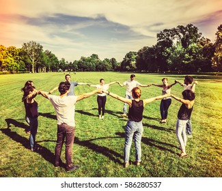 Group of Friends Making a Circle and Holding Hands Together.