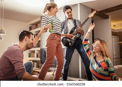 Grupo de amigos que se burlan de la fiesta en casa. Joven negro tocando guitarra eléctrica.