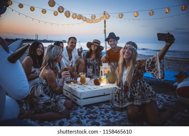 Group of friends making party on the beach at sunset time