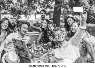 Group of friends making a picnic barbecue and taking selfie with mobile smartphone in park outdoor - Happy people having fun together eating and drinking wine - Friendship, youth lifestyle concept