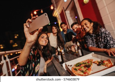 Group of friends making a selfie at rooftop party. Happy young people taking self portrait during party.