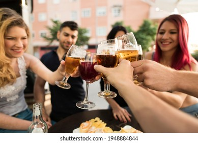 Group of friends making a toast with alcoholic drinks