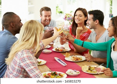 Group Of Friends Making Toast Around Table At Dinner Party