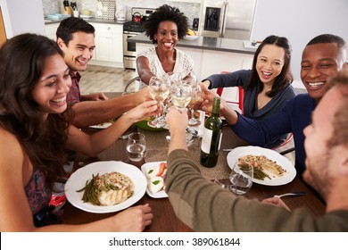 Group Of Friends Making A Toast At Dinner Party