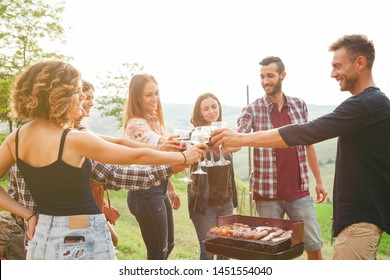 Group of friends making a toast during a barbecue in the country - Millennials having fun together