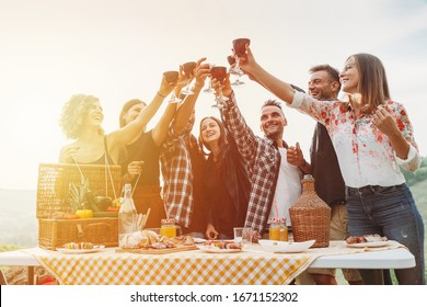 Group of friends making a toast during a barbecue in the countryside - Happy people having fun at a picnic on the hills in summer at sunset