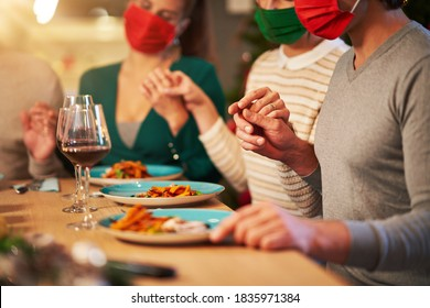 Group of friends in masks praying over Christmas Thanksgiving table at home - Shutterstock ID 1835971384
