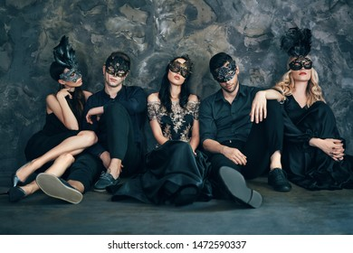Group of friends in masquerade carnival mask sitting on floor relax after party. Beautiful women and men wearing venetian mask. Fashion, friends concept