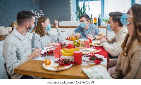 A group of friends in medical masks sit at a festive table