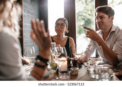 Group of friends meeting at restaurant for dinner. Young men and women having evening meal at cafe.
