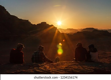 A group of friends meets sundown sitting on the rock in Wadi Rum desert