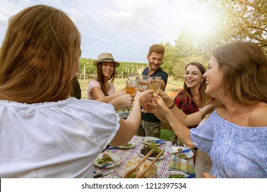 group of friends of millennial generation farmers have a party in the fields beneath vineyard. happy people gathering outdoor concept.