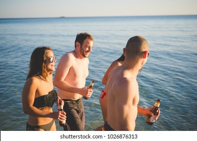 Group of friends millennials drinking beer walking on the beach - happiness, interaction, getting away from it all concept