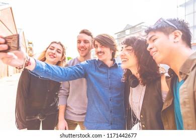 group of friends millennials outdoor using smart phone taking selfie - internet, social network, happiness concept