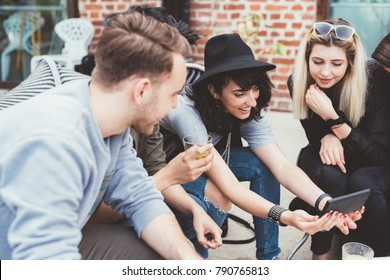 Group of friends millennials sitting outdoor bar using smart phone - technology, internet, happy hour concept