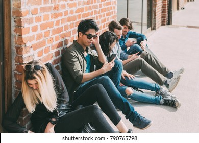Group of friends multiethncit sitting outdoor using smart phone - social network, technology, phubbing concept