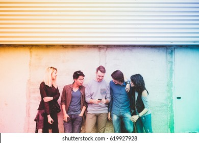 Group of friends multiethnic millennials outdoor using smart phone - technology, social network, togetherness concept - filtered colorful