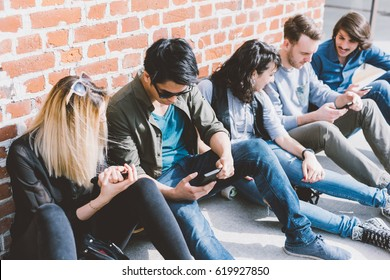 Group of friends multiethnic millennials sitting outdoor using smart phone - technology, having fun, togetherness concept