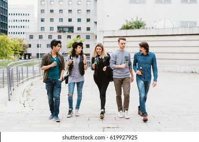 Group of friends multiethnic millennials walking outddor city chatting drinking beer - happiness, togetherness, having fun concept