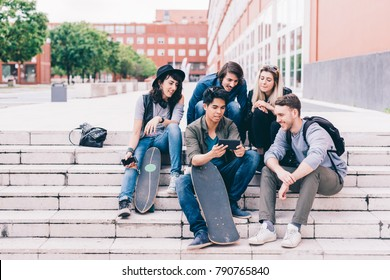 Group of friends multiethnic sitting outdoor using smart phone - technology, phubbing, internet concept