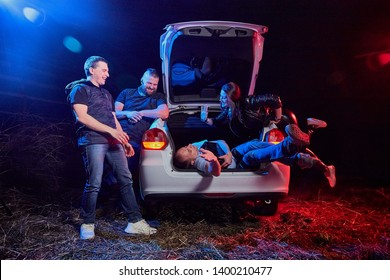Group of friends near the car at night, one drunk guy lying in the trunk and colored red and blue light around. Photoshoot about life of gungsters in Russia