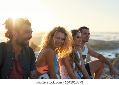 group of friends on beach enjoying summer holiday students having fun vacation hanging out on beachfront at sunset