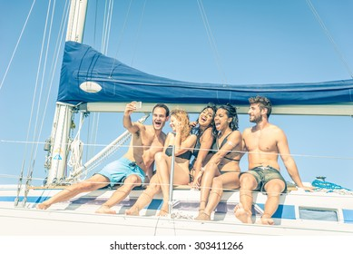 Group of friends on a boat taking a selfie - Multiethnic people having fun and partying on a sail boat - Tourists on a summer vacation