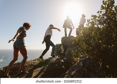 Group of friends on a mountain. Young people on mountain hike on a summer day. Men and women climbing rocks.