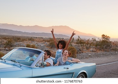 Group Of Friends On Road Trip Driving Classic Convertible Car