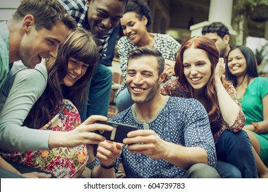 A group of friends on the steps of a house porch, looking at a smart phone selfy on the screen