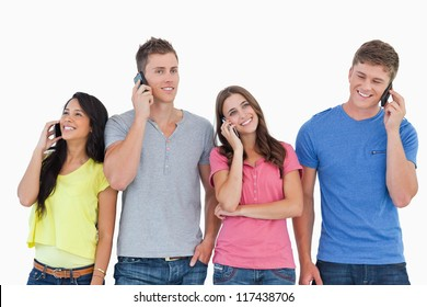 A group of friends on their phones making calls as they smile and stand beside each other