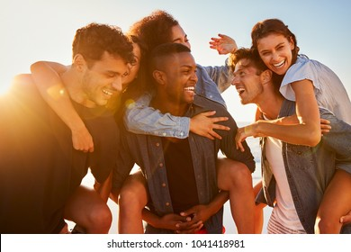 Group Of Friends On Vacation Having Piggyback Race On Beach
