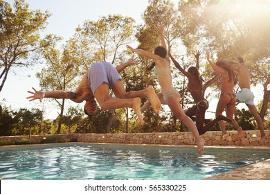 Group Of Friends On Vacation Jumping Into Outdoor Pool
