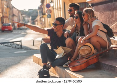 Group of friends on vacation sitting at the city street looking for direction on map.