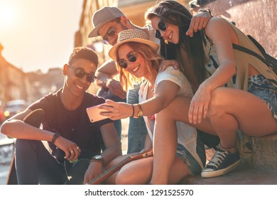 Group of friends on vacation sitting at the city street looking for direction on smart phone.