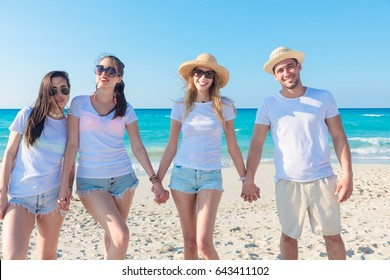 Group of friends on vacation with white t-shirts on the beach laughing and enjoying