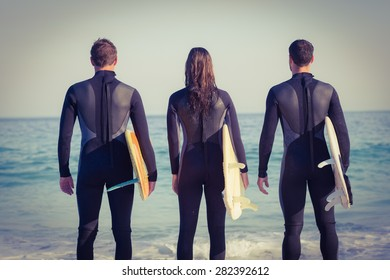 Group of friends on wetsuits with a surfboard on a sunny day