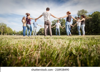 Group of friends at park holding hands. View from below