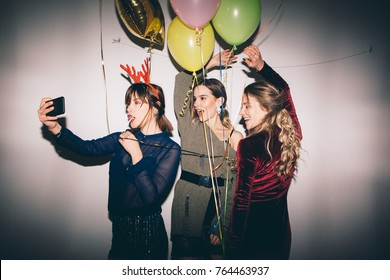 Group of friends at party making selfie and having fun