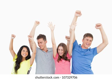 A group of friends party together with their hands in the air