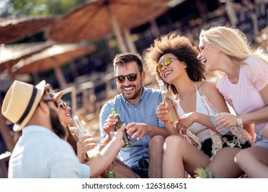 Group of friends partying on the beach.Young people celebrating during summer vacation.
