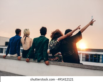 Group of friends partying on terrace with drinks. Young men and women enjoying drinks on rooftop at sunset.