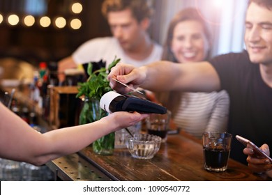 Group Of Friends Paying For Meal In Restaurant