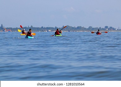 Group of friends (people) travel by kayaks. Kayaking together in wild Danube river and biosphere reserve in summer. Peacefull nature scene of calm river. Water tourism concept